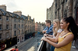 Grassmarket, a historic street in Edinburgh. Three young people on the terrace overlooking the street and terraced houses.